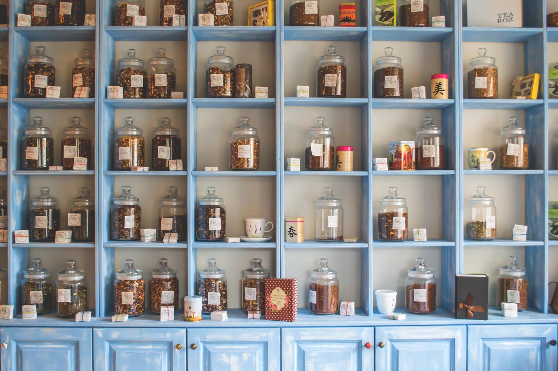 assorted jars on blue shelf cabinets